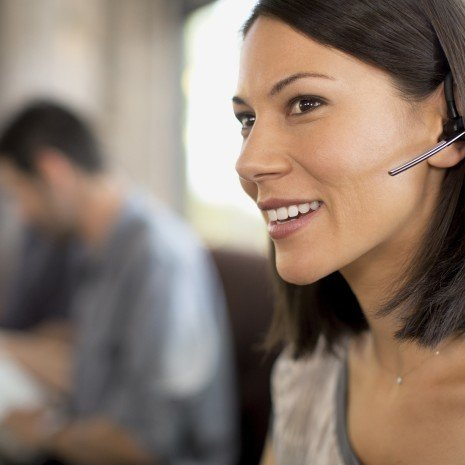Woman in cafe and smiling in conversation while wearing Voyager Legend.